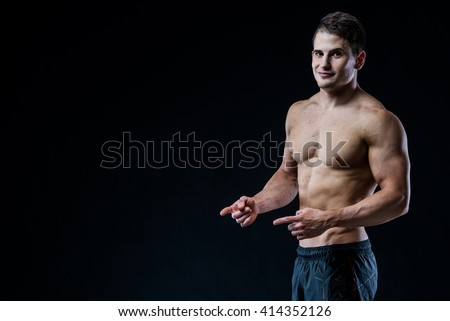 Shirtless muscular athletic man point with two hands and fingers to blank copyspace. Sexy bodybuilder showing his body on black isolated background copy space. - stock photo