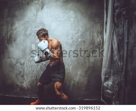 Shirtless muscular fighter in action. Isolated on grey background. - stock photo