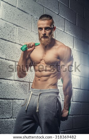 Shirtless muscular guy posing over grey background.