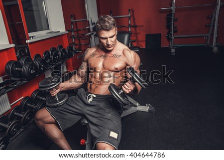 Shirtless muscular man doing biceps workout with dumbbells in a gym club.