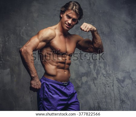 Shirtless muscular man in a blue shorts posing against the grey wall.