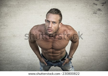 Shirtless muscular man shot from above, looking at camera, standing outdoor - stock photo