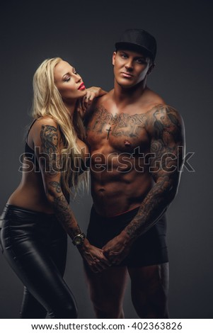 Shirtless muscular tattooed man in a cap and sexual blond female posing in studio in deep shadows.