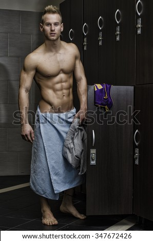 Shirtless muscular young male athlete in gym dressing room, smiling with towel around waist - stock photo