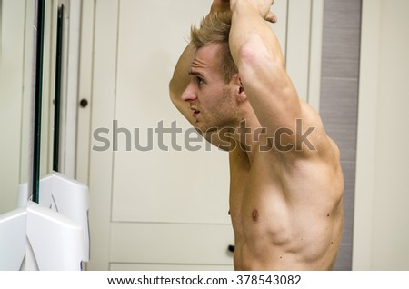 Shirtless, muscular young man, towel around waist, looking at his hair in bathroom mirror - stock photo
