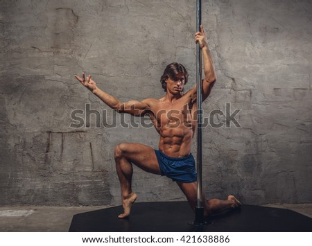 Shirtless  pole danceron knees on a grey background.
