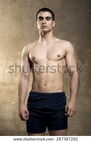 Shirtless strong man posing in studio shot near to wall