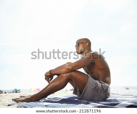 Shirtless young man sitting on beach looking away. Thoughtful young male model relaxing on beach with copyspace. - stock photo