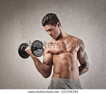 Shirtless young man with the left arm tattooed raising a dumbbell with the right arm - stock photo