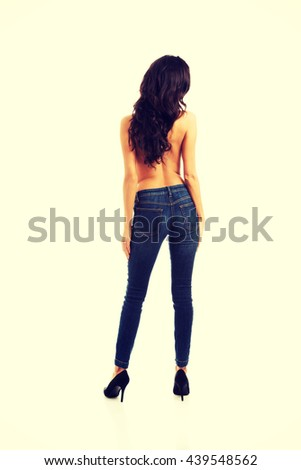 Shirtrless woman standing in jeans back to camera - stock photo
