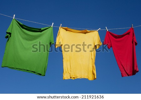 Shirts on clothesline against blue sky.