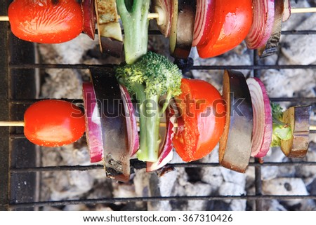 shish kebab fresh raw vegetables tomato red onion cherry broccoli eggplant on skewer over grid charcoal brazier ready to cook - stock photo