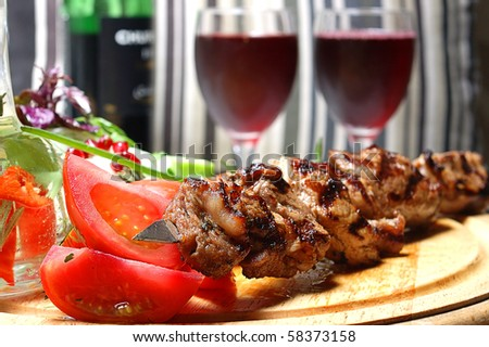 Shish kebab on a wooden support with vegetables and spices - stock photo