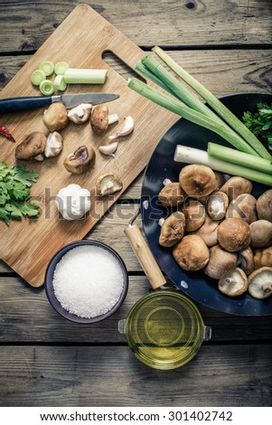 shitake mushroom prepare for cooking on wok and chopping block with ingredients - stock photo