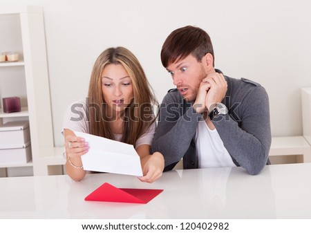 Shock portrayed on man's face after reading letter. - stock photo