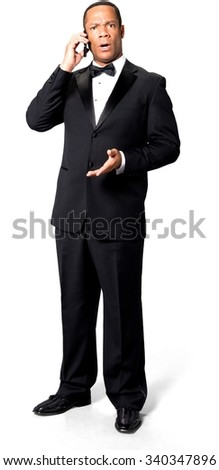 Shocked African man with short black hair in evening outfit using mobile phone - Isolated - stock photo