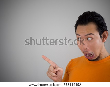 Shocked and surprised face of Asian man look into empty space. - stock photo