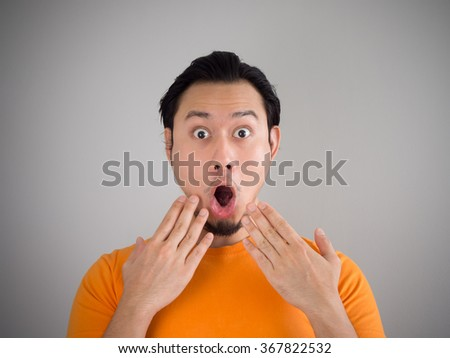 Shocked and surprised face of Asian man with his hand on his chin. - stock photo