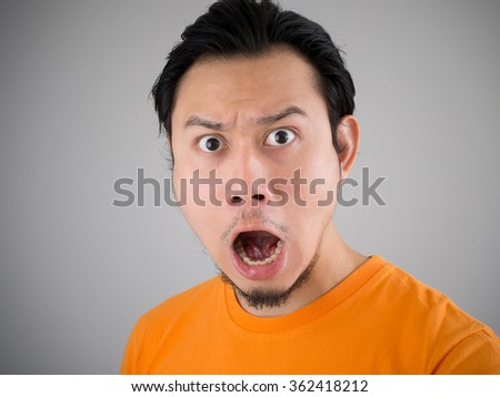 Shocked and surprised face of Asian man with his jaw drops. - stock photo