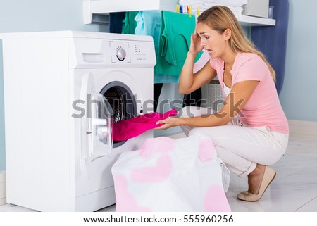 Shocked Angry Woman Looking At Bleached And Stained Cloth In Washing Machine At Laundry Room