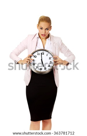 Shocked business woman holding office clock - stock photo