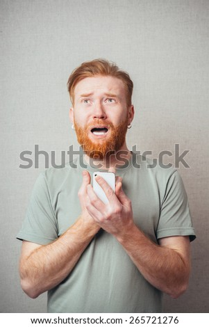 Shocked businessman Beard reads the message on the phone bad news - stock photo