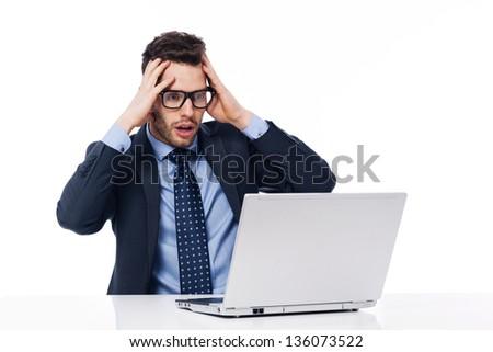 Shocked businessman looking at laptop - stock photo