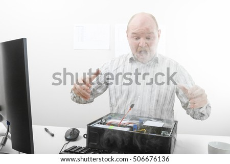 Shocked Businessman Looking At Smoke Coming Out From Computer