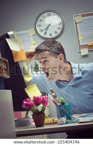 Shocked businessman staring at computer screen with mouth open. - stock photo