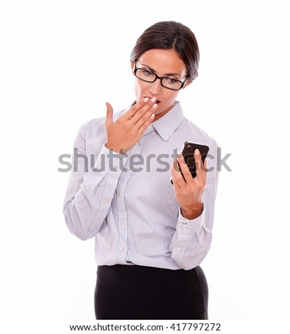 Shocked businesswoman looking at her cell phone making a surprised gesture with one hand to her mouth while wearing her straight hair back and a button down shirt on a white background - stock photo