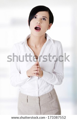 Shocked businesswoman looking up - stock photo