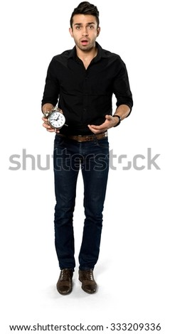 Shocked Caucasian man with short dark brown hair in casual outfit holding alarm clock - Isolated