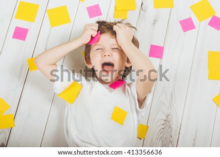 Shocked child with empty stickers on his body. Stress from studying, doing homework. - stock photo