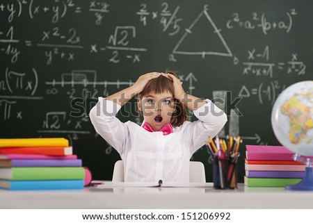 Shocked cute pupil in classroom  - stock photo