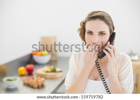 Shocked cute woman phoning in her kitchen with a telephone looking at camera - stock photo