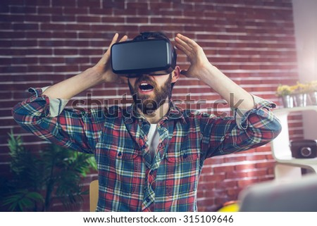 Shocked editor wearing 3D video glasses with hands raised at office - stock photo