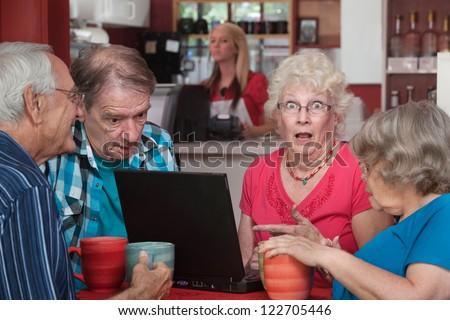 Shocked female senior adult with wide eyes and laptop - stock photo