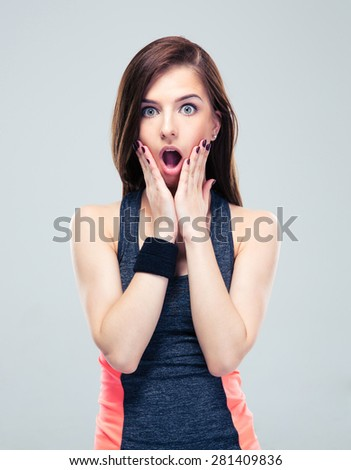 Shocked fitness woman in sportswear standing on gray background. Looking at camera - stock photo