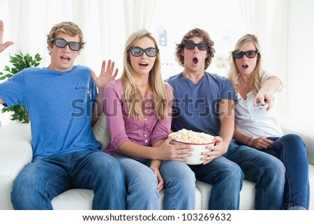 Shocked friends with some popcorn as they get scared by a scary movie - stock photo