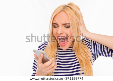 Shocked frustrated young woman holding phone and screaming - stock photo