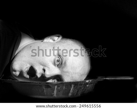 Shocked Head in a Cast Iron Skillet on Black - stock photo