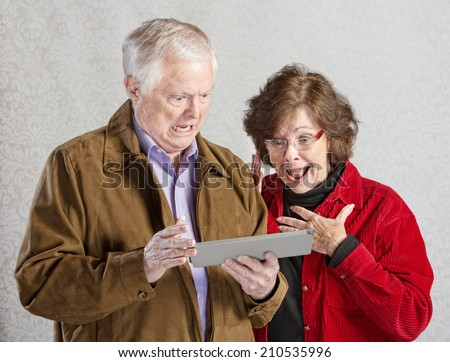 Shocked man and woman looking at computer tablet - stock photo