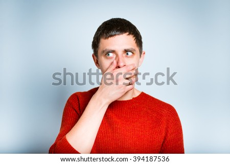 Shocked man closing mouth with hands, isolated on a gray background