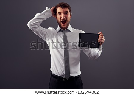 shocked man holding tablet pc and screaming. studio shot over dark background - stock photo