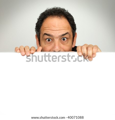 Shocked man peeking behind a blank white billboard - stock photo