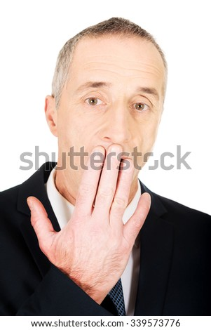 Shocked mature businessman with hand on mouth - stock photo
