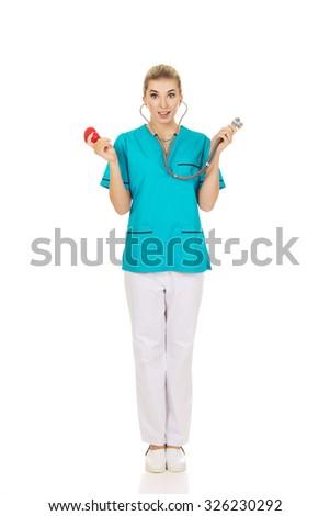 Shocked nurse or female doctor holding stethoscope and heart model - stock photo