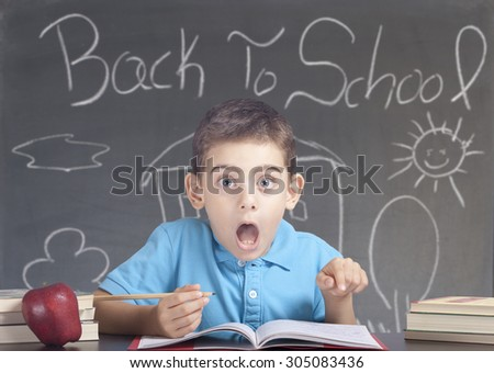 Shocked schoolboy in classroom - stock photo