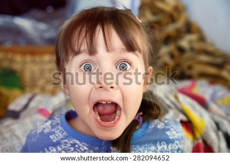 Shocked screaming little girl with opened mouth in her bedroom - stock photo