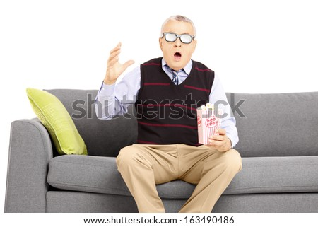Shocked senior man with popcorn box sitting on a sofa and watching movie isolated on white background - stock photo